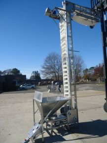 """1-USED NEDCO """"ULTRA  LIFT""""  Z-SHAPED APPROX. 15 FT. DISCHARGE HEIGHT STAINLESS STEEL BUCKET ELEVATOR.  EQUIPPED WITH 3 FT. LONG INFEED SECTION AND 80 IN. LONG TOP REACH SECTION.  BUCKET ELEVATOR ALSO HAS APPROX. 42 IN. X 42 IN. STAINLESS STEEL PRODUCT HOPPER WITH FMC SYNTRON VIBRATORY FEEDER.  EQUIPPED WITH APPROX. 6 IN. X 12 IN.  FDA WHITE POLY CARBONATE BUKETS."""