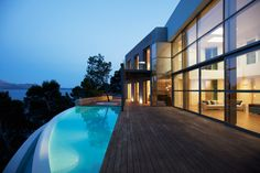 The large floor-to-ceiling windows of this modern home make both the view and the infinity pool visible from the open-concept living space. This wood and stone patio also has a small hot tub big enough for two.