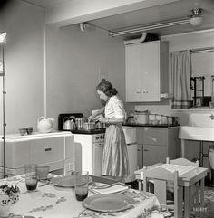 May 1942. Greenbelt, Maryland, federal housing project. Mrs. Leslie Atkins preparing dinner in her kitchen, one end of which is the dining room. Notice the mangle and washing machine on either side of the stove. Medium format negative by Marjory Collins for the Office of War Information.
