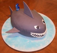 Shark cake - Made this cake for my son's 5th birthday. Used the Wilton footbal pan, rolled fondant with gumpaste added for the fins, rolled fondant for the rest, and the durable chocolate cake recipe from heartsfire (http://cakecentral.com/recipes/6093/durable-cake-for-3d-in-chocolate). Delicious cake, by the way - thick as pound cake, and so tasty!