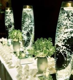 Baby's breath submerged in a glass or vase of water w/a floating candle