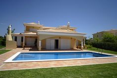 Suburban yellow stucco home with minimalist backyard pool with wrap-around patio.  Grass surrounds the patio and pool.