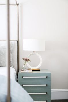 A modern blue nightstand accented with a white mosaic ring lamp sits beside a silver canopy bed dressed in white and blue bedding. Brooke Wagner Design
