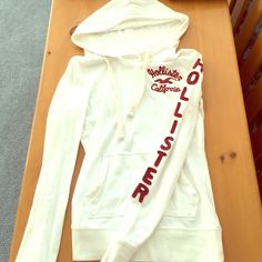 Tight fitting Hollister hoodie Worn but overall good condition. It is a white sweatshirt so it's almost possible for it to be spotless. A small tear in the top (in picture) and small stain on the front (in picture). Size XS. Hollister Tops Sweatshirts & Hoodies
