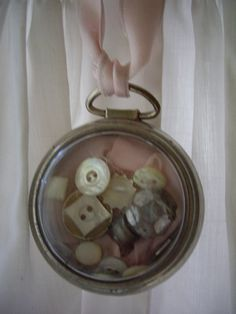 collection of buttons in a vintage pocket watch case