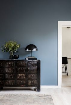 Colour is briefly introduced in the living room, which has a slate-blue feature wall and murky green painting by artist Anette Wier. Blue Wall Colors, Room Wall Colors, Living Room Colors, Blue Feature Wall Living Room, Kitchen Feature Wall, Blue Living Room Walls, Slate Blue Walls, Blue Walls In Kitchen, Blue Painted Walls