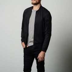 """We've re-worked the classic """"MA-1"""" bomber jacket to give it a contemporary look and feel. A smooth-finished brushed cotton fabric and black metal zippers transform this sportswear piece into a polished layer suited for all seasons. We love this iconic staple piece paired with clean-cut denim and a simple t-shirt for an elevated but casual look that never goes out of style."""