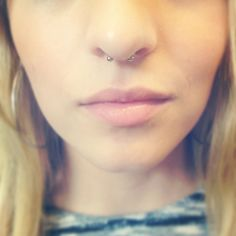 Septum piercing with small curved barbell.
