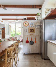 Além de servir como divisão entre ambientes, o fundo do armário foi decorado com pratos de parede e utensílios de cozinha.