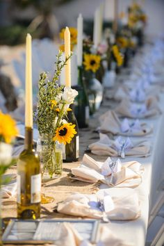 Simple flowers beside candlesticks in wine bottles