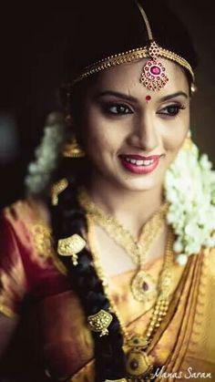 Traditional Southern Indian bride wearing bridal saree, jewellery and hairstyle. #BridalMakeup #TempleJewellery #MaangTikka
