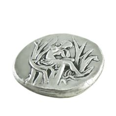 Handmade silver-plated copy of the silver stater coin of Gortyn, depicting Europe on the obverse of the coin and Zeus transformed into a calm bull, on the reverse. 325 B.C., Gortyn, Crete The coin is offered in an acrylic case for protection and better presentation. Diameter of the coin: 2,6 cm  Dimensions of the acrylic case: 5 cm x 6 cm x 5 cm