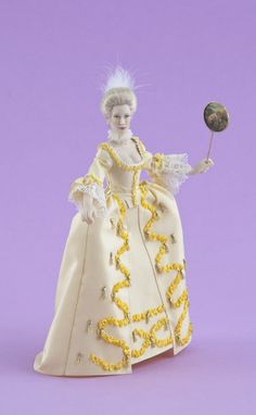 NAME: Erica - PERIOD: late 18th century. Doll in a court dress (French gown) made out of taffeta silk and adorned with ribbon work and tassels. Silk slippers. Fixed fan included.