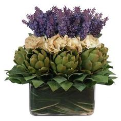 Silk lavender and artichokes with lemon leaves in a square glass pot.  Product: Faux floral arrangementConstruction Material: Silk, plastic and glassColor: Purple, creme and greenFeatures: Includes faux lavender and artichokeDimensions: 14 H x 12 W x 12 D Note: For indoor use only