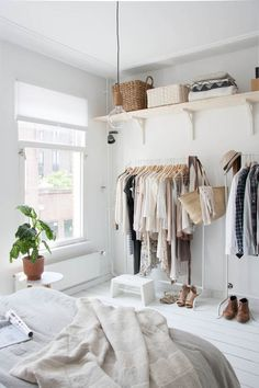 A light, bright bedroom.  Racks are a great solution to lack of closet space.  Plus, out of sight, out of mind.  Seeing your clothes keeps the clutter to a minimum and reminds you to wear what you have.