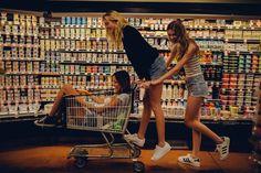 Chicas jugando con un carrito de super mercado