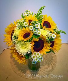 Fall bridal bouquet with various sizes of sunflowers, white mums, solidago, and white monte casino asters.