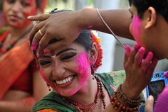 Indian revelers cover each other with colored powder look on during Holi festival celebrations in Siliguri, on March 27, 2013. (Diptendu Dutta/AFP/Getty Images)