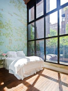 Restful white bed in a room with huge windows and blue  floral wall paper.