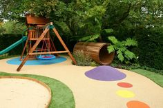 Idee für einen Spielplatz mit Rutsche, Tunnel, Schaukel und buntem Bodenbelag