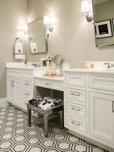 Exquisite bathroom boasts separate his and her washstands placed below…
