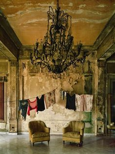 This is such clever styling, the contrast of the glamorous chandelier next to the hanging washing is wonderful