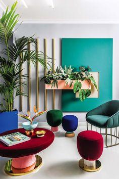Una oficina con tonos vibrantes inspirada en el trabajo del emblemático estudio de arquitectura y diseño industrial Memphis. Rosa, azul, rojo, durazno y verde combinan perfecto con toques de dorado y plantas tropicales.