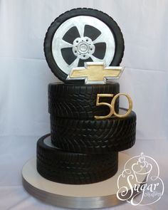 "https://flic.kr/p/dPY8FG | stack of tires cake | This was for a surprise 50th birthday party. The birthday boy has a '68 Camaro and I've been itching to do a ""stack of tires"" cake. I used two 13"" tiers and two 11"" tiers. - gumpaste # 50 and Chevy logo, cut freehand. Tire tread was also freehand with a modeling tool -- dark chocolate fondant lightly airbrushed black"