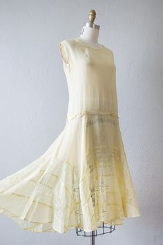 1920's light yellow sheer crepe dropped waist dress features shell bodice, delicate silk ribbon around the waist accented with little flowers, and lace panels all along the skirt. Dress has side snap closure and a single snap closure on the shoulder.