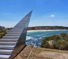 """Optical Illusion Stairway To Heaven. """"David McCracken's 'Diminish and Ascend', a giant aluminum sculpture that looks like a stairway to heaven. It doesn't actually lead to the pearly gates though, it's just an optical illusion. It's really only 30-feet long and 15-feet high and is perched atop a hill at Bondi Beach in Australia."""""""