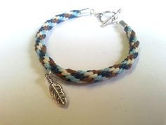 A handmade toggle bracelet made with a kumihimo braid of blue and brown colours, with a choice of charm.