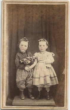 Antique photo of brother and sister, little girl holding her doll.