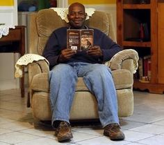 Earl Mills sits with the first book he ever read, 'Along the Gold Rush Trails' by Gail Wilson Kenna. Illiterate much of his life, he was 48 when he read it.