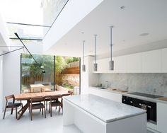 White minimal kitchen with great natural light and pendants over the island