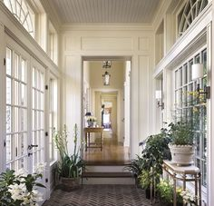 Herringbone brick floored garden room/entrywith french doors, and symmetrical windows opposite, sconces, lovely millwork, beadboard ceiling,and beautiful semi-circular transom windows leads into the main hallway of the house