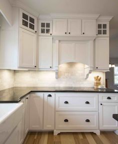 Kitchen with white inset shaker cabinets. Stacked glass cabinets. Custom hood with corbels. Hickory wood floors. Built in microwave and pantry units. Island with turned post legs. Black granite counters. White hood.