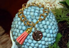This is a brand new personalized bracelet from Designs by Devra! The price includes the gold bracelet, coral tassel, and your engraved initials.