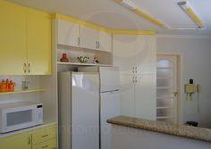 A cozinha é ampla e completa, equipada com bancadas em granito cinza, dois refrigeradores, eletrodomésticos da linha branca e armários planejados em um suave tom de amarelo, que irradia as boas energias da praia para os convivas. — em Edmundo Imóveis.