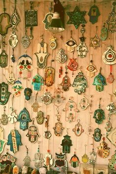 A wall full of amulets - mostly hamsas...but I see a Star of David,evil eyes, doves of peace, olive branches, and pomegranites...all bringing protection and good luck to the wearer or home.