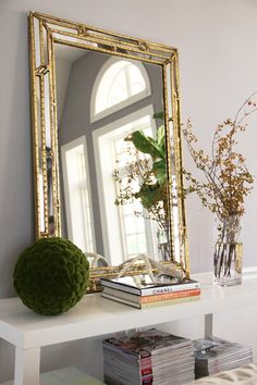 I like this whole step up. The mirror is lovely, the color of the moss ball, and the stacks of magazines and books.