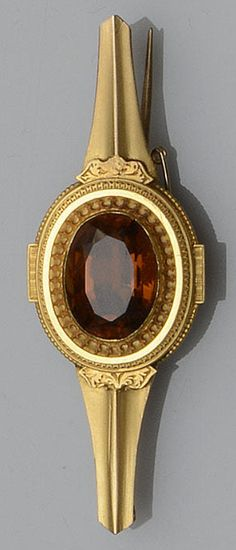 A citrine bar brooch  The oval mixed-cut citrine within a stepped collet setting, pierced and embossed with stylised foliate and geometric borders, to a tapered bar mount applied with foliate engraved panels, length 6.1cm. Victorian or Victorian style.