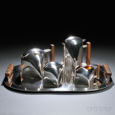 Gabriele De Vecchi (Italian, b. 1938) Five-piece Tea Service   Sterling silver, wood   Italy, post 1968, retailed by Calderoni Gioielli   Angular streamline design, including tray, coffeepot, teapot, sugar, and pitcher, all with exception of covered sugar having wood handles, all marked De Vecchi Calderoni Gioielli 925, post-1968 mark, D in a circle, crown mark, approx. total wt. 116 troy oz., ht. 3 1/4 to 7 1/4, tray lg. 19, wd. 14 1/2 in. Accompanied by a pamphlet in Italian
