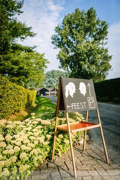 Vintage schoolbord met silhouetten van het bruidspaar, neergezet ter indicatie van de plaatsen voor het parkeren en het feest tijdens deze tuinbruiloft.