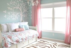 Blue and pink girl's room with tree mural