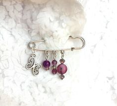 Silver safety pin brooch, with butterfly charm, purple shell and agate beads, and purple crystals
