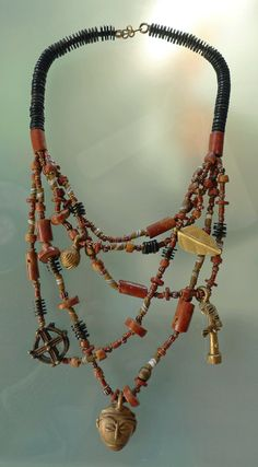 """Blend of brown and red tones of African and Venetian glass, bauxite, black and brass heishi and a mix of """"Gold-weight"""" charms from Ghana! Shortest strand is 18″, longest strand is 25″ with 1″ mask"""
