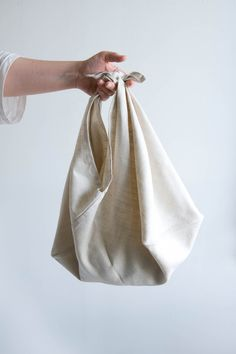 The Azuma is a Japanese bag. An ingenious construction made from a single piece of cloth, its roots are in the beautiful simplicity of the furoshiki cloth. Triangle Bag, Japanese Bag, Diy Sac, Self Design, Linen Bag, Simple Bags, Cotton Bag, Cloth Bags, Fashion Bags