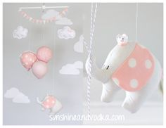 Pink elephant baby mobile, nursery decor for a travel theme nursery. A little traveling elephant floating too far away adventures hanging onto 3 little balloons. A perfect addition to your travel or circus theme nursery décor. The little elephant and balloons are all hand made from fabric and strung onto a wooden dowel with clear string. Finished with two little clouds and top bunting flags. The little clouds can be personalized with a name or a short saying.*(see note at the bottom)…