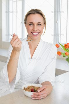 Smiling woman in bathrobe having cereal at home in the kitchen ...  30s, Abode, Dressing Gown, Looking At Camera, Mid Adult, apartment, bathrobe, bowl, breakfast, calm, caucasian, cereal, cheerful, content, domicile, eating, female, flower, happy, having, healthy, home, homey, house, household, indoors, kitchen, leisure, lifestyle, morning, orange, peaceful, portrait, relaxing, sitting, smiling, spoon, tulip, woman