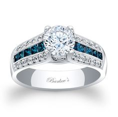 This sophisticated, vintage, three row diamond engagement ring sports a round prong set diamond center. The three row shank features a center row of channel set princess cut Blue diamonds with flanking rows of pave set round diamonds. A milgrain finish adds the final touch of elegance to this classic ring.<br />  <br />  Also available in rose, yellow gold, 18k and Platinum.